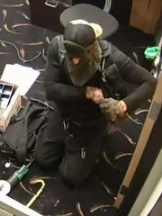Police believe the suspect in the July 18 robbery of Manitowoc's Carmike Cinema has experience in climbing or working in a field that requires ropes and safety equipment. Pictured is the suspect in a surveillance video still from the robbery.