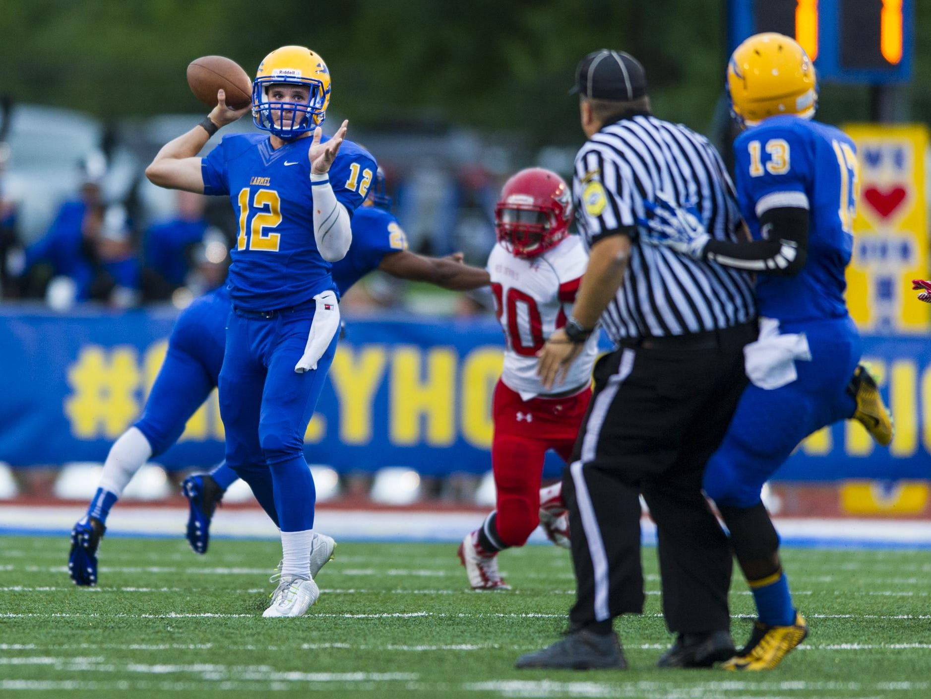 Carmel High School junior Michael Viktrup (12) pass the ball out of the backfield during the first half of action. Carmel High School hosted Pike High School in varsity football action, Friday, September 12, 2014.
