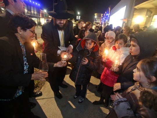 Rockland County legislator Aney Paul and Rabbi Chaim Zvi Ehrenreich of The Chabad Jewish Enrichment Center in Chestnut Ridge help children light candles during a Hanukkah menorah lighting ceremony at The Shops at Nanuet Dec. 2, 2013. Rabbi Ehrenreich led the ceremony, which was sponsored by The Shops at Nanuet an Fairway Market. Children and adults were treated to traditional potato latkes, donuts, and hot chocolate. ( Seth Harrison / The Journal News )