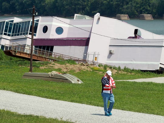 Owner Jeff Ruby walks away after looking at the partially sunken Waterfront Restaurant.