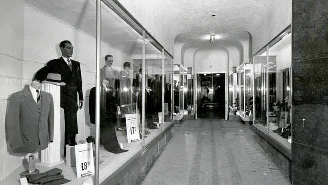 "From March 24, 1941: ""New Mills Street arcade and display windows of the White House Department Store are shown. Striking aluminum banding and joisting, coupled with heavy plate-glass, give the four windows an ultra-modern appearance. The heavy plate glass door entering the men's wear department from the arcade is half-inch thick Herculized glass, drilled to allow placement of modernistic aluminum hardware. The building of the new arcade allows traffic to pass through to the Mills Building Lobby at night when the department store is closed. Modern fluorescent lighting is used in all four windows. The windows will be used exclusively for the display of men's clothing and footwear. Construction work has taken four weeks, and was done by H.T. Ponsford and Sons. The firm of Trost and Trost did the architectural work."""