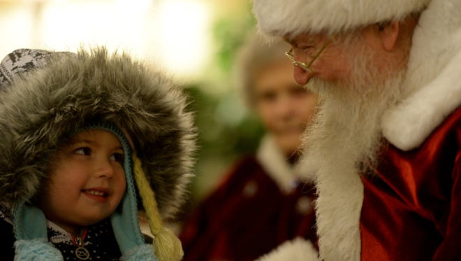 Santa Claus talks with Zoey Rader inside the Richmond Furniture Gallery in the Depot District during last year's Old Fashioned Christmas Festival.
