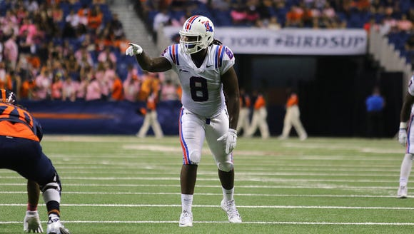 Louisiana Tech defensive end Vontarrius Dora signals