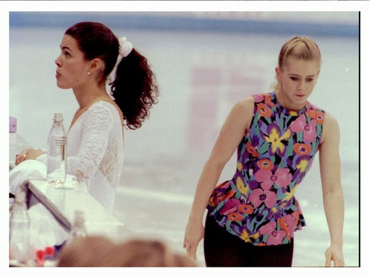 Tonya  Harding, right, skates by as Nancy Kerrigan talks to her coaches during a training  session Feb. 17, 1994, at the Winter Olympics in Lillehammer, Norway. Kerrigan and Harding skated on the same Olympic ice for an hour but never acknowledged each other's  presence.