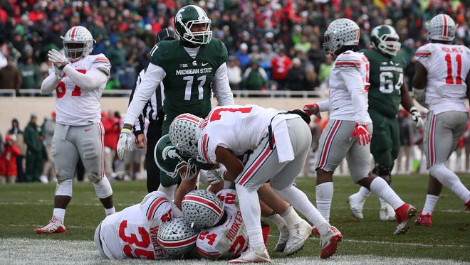 Ohio State's Chris Worley (left) and Malik Hooker (right) combine on an interception (credited to Worley) on Michigan State's failed two-point conversion attempt, preserving OSU's 17-16 lead.