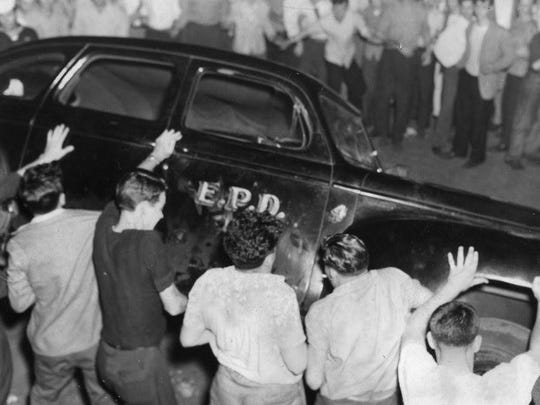 This photo shows a group of young people overturning a police radio cruiser, one of two damaged during the riot.  After eight bingo operators later turned themselves in to police and were arrested, their bingo equipment was confiscated.  Several others involved in the riot outside of the Union Club were also arrested for disorderly conduct and damage to public property.