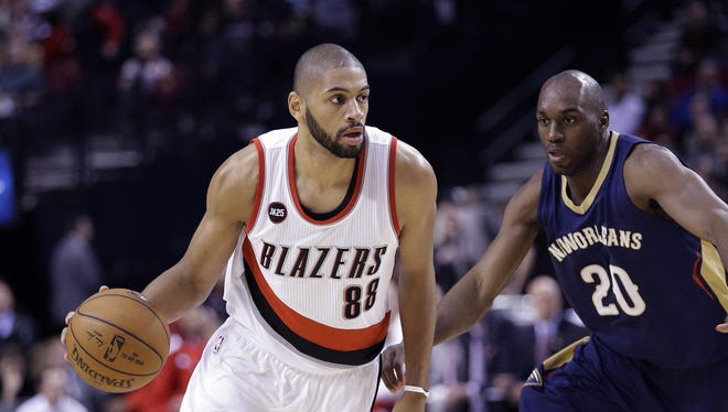 Portland Trail Blazers forward Nicolas Batum, from France, left, drives past New Orleans Pelicans forward Quincy Poindexter during the first half of an NBA basketball game in Portland, Ore., Saturday, April 4, 2015.