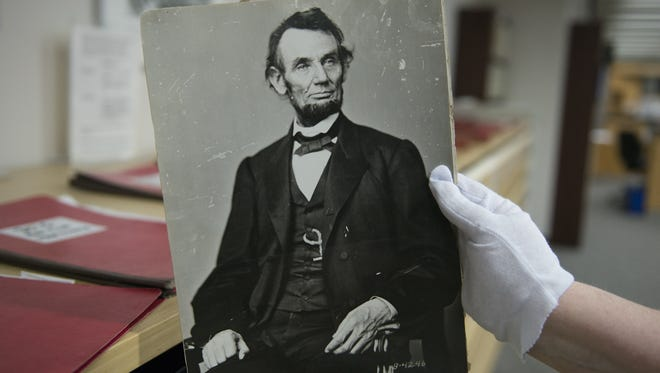 Karen Needles holds up a photograph of President Abraham Lincoln at the National Archives in College Park, Maryland. Three blocks away, 150 years earlier, Lincoln was felled by an assassin's bullet.