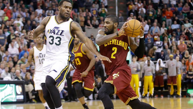 Cleveland Cavaliers' Kyrie Irving (2) drives to the basket  as Utah Jazz's Trevor Booker (33) defends in the second half during an NBA basketball game against the Utah Jazz Wednesday, Nov. 5, 2014, in Salt Lake City.