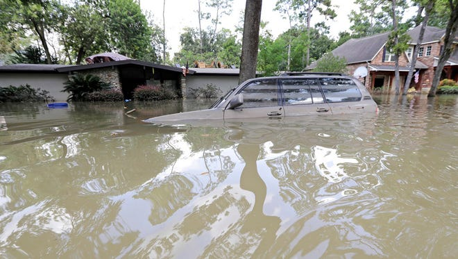 FILE - In this Sept. 4, 2017, file photo, a car is submerged in floodwater in the aftermath of Hurricane Harvey near the Addicks and Barker Reservoirs in Houston. Many homeowners in several suburban Houston subdivisions who were flooded during Harvey's torrential rainfall are questioning if local officials did enough to warn them a nearby reservoir could overflow during a heavy storm event and inundate their homes. (AP Photo/David J. Phillip, File)
