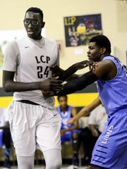 Tacko Fall of Liberty Christian Prep battles for position in the paint with Udoka Azubuike (35) of The Potter's House during Tuesday's game in Tavares.