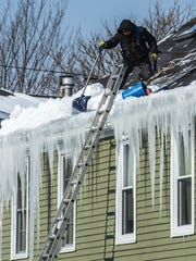 A roofer shovels snow off a roof to clear an ice dam