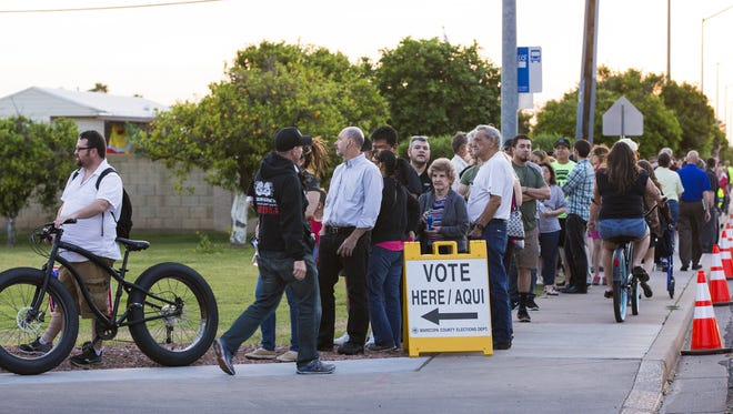 Voters wait in line at Pilgrim Evangelical Lutheran Church in Mesa on Tuesday.