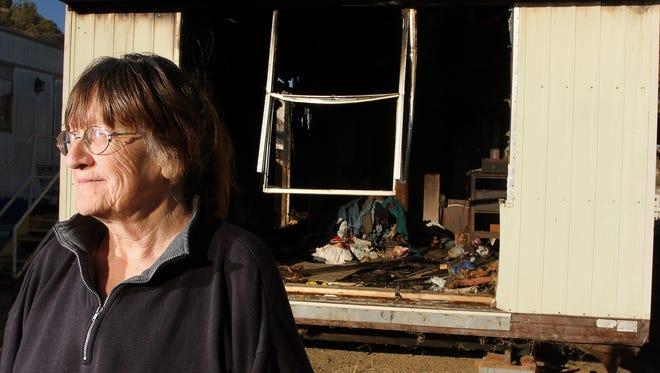 Kathy Chavez stands outside the charred remains of her mobile home on Saturday on Crouch Mesa.