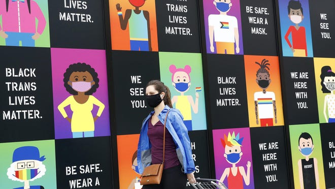 A woman wears a face mask to protect against the spread of the new coronavirus as she walks past artwork on a storefront, Wednesday, June 17, 2020, in Washington.