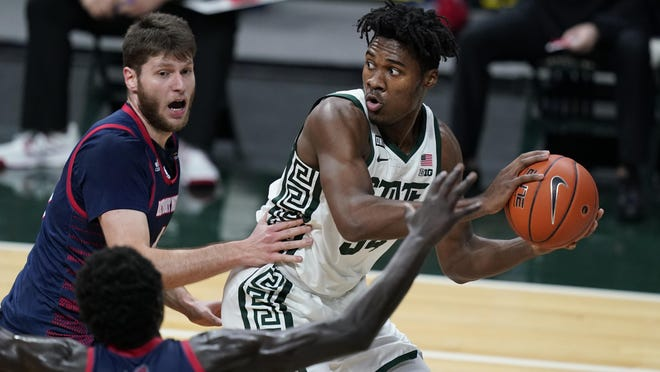 Michigan State forward Julius Marble II (34) looks to pass as Detroit Mercy forward Willy Isiani defends during the first half of an NCAA college basketball game, Friday, Dec. 4, 2020, in East Lansing, Mich.