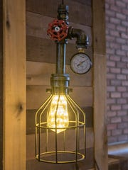 """""""Gas-pipe"""" lighting hangs over tables at Park Place Gastro Pub."""