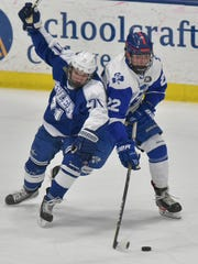 Catholic Central's Dylan Montie (22) battles against Salem's Colin Goleniak (71).