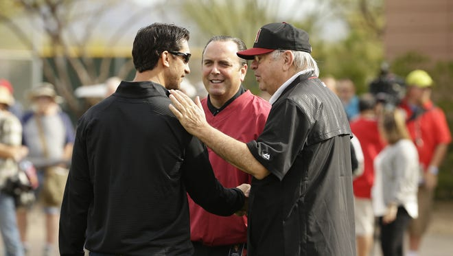 Arizona Diamondbacks GM Mike Hazen, President & CEO Derrick Hall and managing general partner Ken Kendrick (right) huddle at the first day of spring training camp on Feb. 14, 2017 at Salt River Fields in Scottsdale, Ariz.