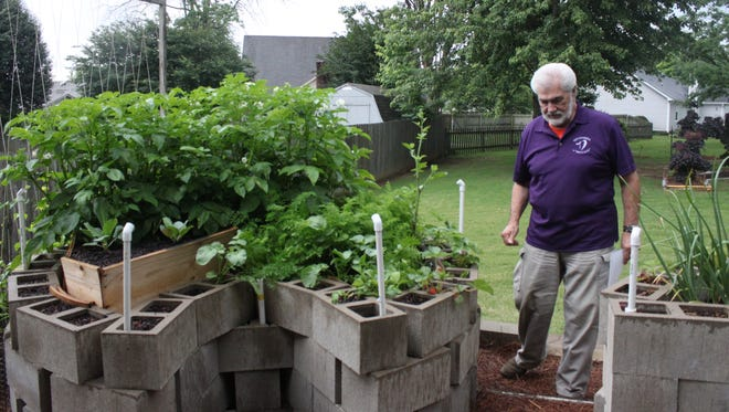 Johnny White walks past one of his keyhole gardens, a type of raised bed he read about in The Jackson Sun.