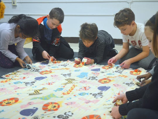 First-, second- and third-grade students in the Jewish Community Center Kids Connection program work on a blanket for Mom's House.