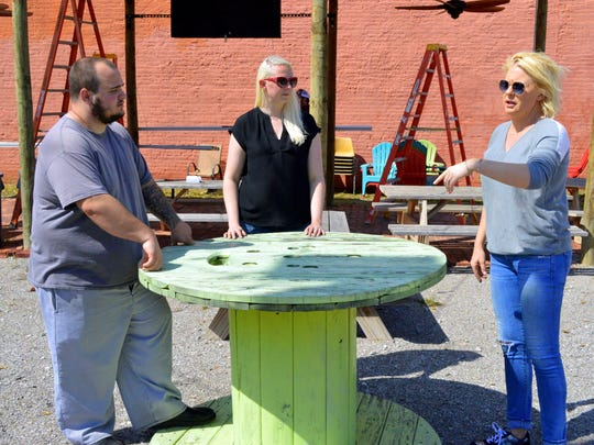 Amber Schacter (right), owner of The Yard, A Ganache Company, talks with executive chef Kyle Dalka, left, and Makenzie Snead, about arrangement of picnic tables and other items Thursday at the downtown food truck park. The Yard will open Friday at 5 p.m.