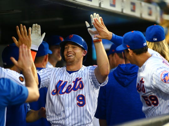 New York Mets left fielder Brandon Nimmo (9) celebrates with teammates in the dugout after hitting a two run home run against the Chicago Cubs during the third inning at Citi Field.
