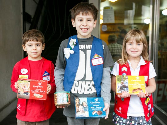 Gus Kreutz-Gallardo, Oscar Kreutz-Gallardo, and Emery Vaughn hold up sweet treats for sale at Holding Court on Tuesday, Jan. 10, 2017. Money raised will support the kids going on a campout to further their environmental education.