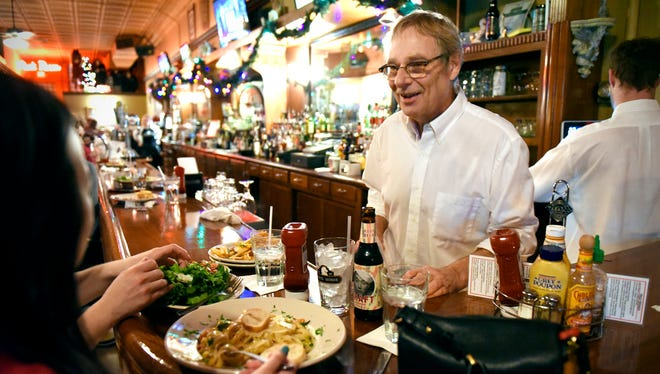 Owner Brian Lee talks to customers while tending the bar at the White Horse.