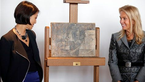 """French Minister of Culture and Communication Fleur Pellerin, left, and Jane D. Hartley, U.S. Ambassador to France, right, pose next to """"La Coiffeuse,"""" or The Hairdresser, a $ 15 million Picasso painting, found in New Jersey, during a presentation at Beaubourg Pompidou Center Museum in Paris, France, Thursday, Sept. 24, 2015. This Picasso artwork, painted in 1911, is going back on display in a Paris Museum after it disappeared from a French storage room more than a decade ago, then turned up in a package from Belgium to New York last year. (AP Photo/Francois Mori)"""