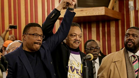 Rev. Jesse Jackson holds up the hand of Judge Greg Mathis in front of a crowd at Metropolitan Baptist Church in Flint.