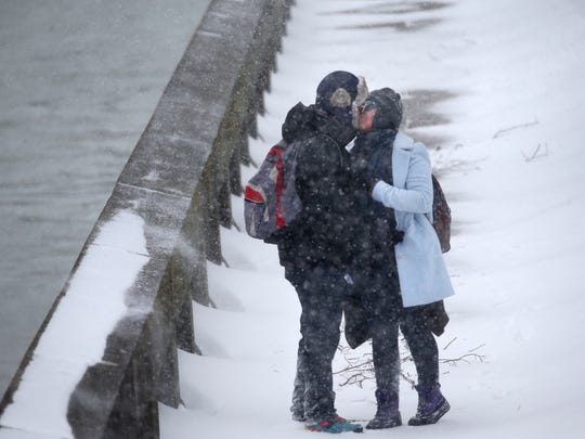 Will Costello and Paula Simpson steal a kiss while making their way home along the river walk from the Rochester Central Library during the beginning of the snowstorm, Stella. FROM MAX: What I love about this photo is it shows that we know how to embrace our weather.
