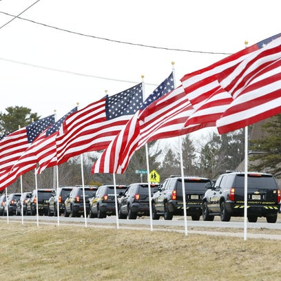 Flags and law enforcement vehicles line a road during