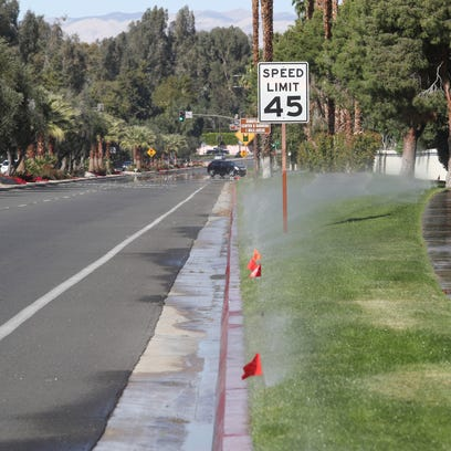 Sprinklers spray grass between the sidewalk and the