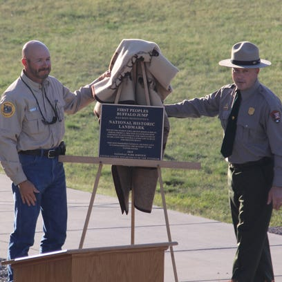 Park officials unveil a plaque honoring First Peoples