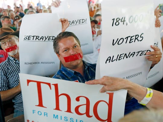 Tea party member Grant Sowell, center, and other supporters of state Sen. Chris McDaniel, hold protest signs and have taped their mouths in a silent protest during the speech of incumbent U.S. Sen. Thad Cochran, R-Miss., at the Neshoba County Fair in Philadelphia, Miss., Thursday, July 31, 2014. Cochran defeated McDaniel in their GOP runoff election for the party nomination. The fair is a traditional gathering place for politicians, area residents, business leaders, voters and families. (AP Photo/Rogelio V. Solis)