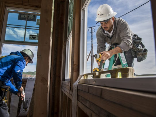 Contractors install a window on a home under construction