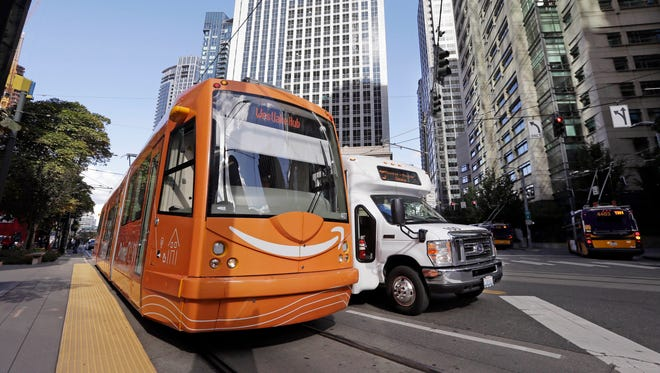A downtown streetcar is wrapped in an ad for Amazon as it waits for passengers in Seattle.