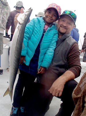 Joline Smith, 7, poses with her father, Jesse Smith and the 10-pound barracuda she caught while fishing on the Gentleman.