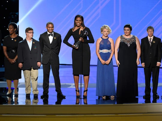 Daina Shilts of Neillsville, in blue dress, along with former First Lady Michelle Obama and seven other Special Olympic athletes present the Arthur Ashe Courage Award to the late Eunice Kennedy Shriver during the 2017 ESPY Awards on Wednesday, July 12, 2017.