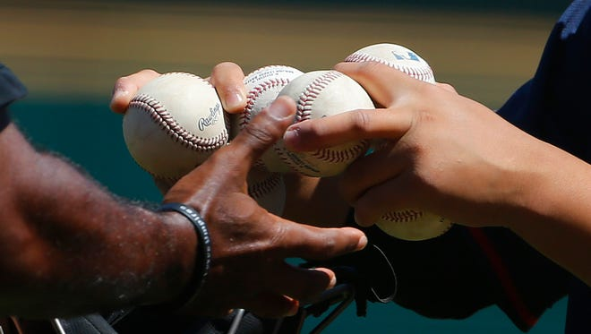 Umpire Alan Porter, left, gets a delivery of game baseballs from a bat boy prior to the first inning of a spring training baseball game between the Cleveland Indians and the Seattle Mariners Tuesday, March 31, 2015, in Goodyear, Ariz.