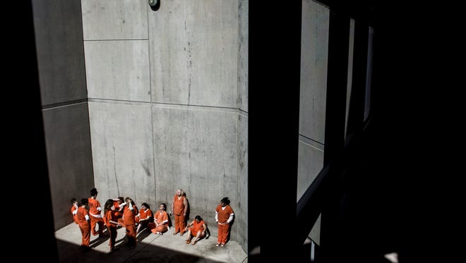 Inmates in the female pod relax outside during a brief moment of sunlight Wednesday, March 16, 2016 at the St. Clair County Jail.