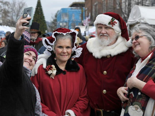 Lacy Miller, left, and Jane Nord pose for a photo with Santa and Mrs. Claus during the 33rd Annual Dickens of a Christmas in downtown Franklin, Tenn. on Saturday, Dec. 9, 2017.