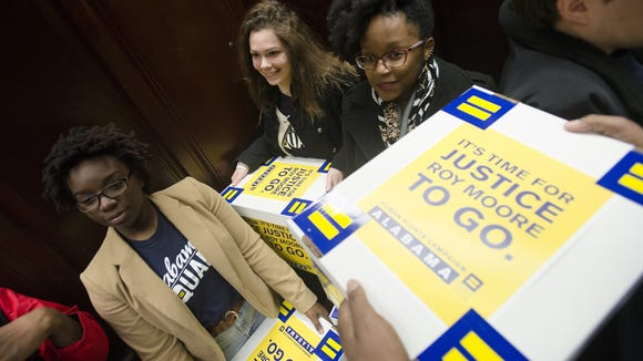 From left, Shanté Wolfe, Eline Roillet and Ashley Gibbons carry boxes with a 28,000 petitions to the Judicial Inquiry Commission urging a full ethics investigation into Alabama Supreme Court Chief Justice Roy Moore's efforts to block probate judges from complying with a federal ruling striking down the state's discriminatory same-sex marriage ban on Wednesday, Feb. 18, 2015, in Montgomery, Ala.