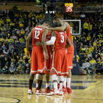The Ohio State men's basketball starters with seniors' Sam Thompson (12), Shannon Scott (3) and Amir Williams (right) meet at half-court during the second half of a game at Michigan earlier this year in which the Buckeyes lost 64-57.