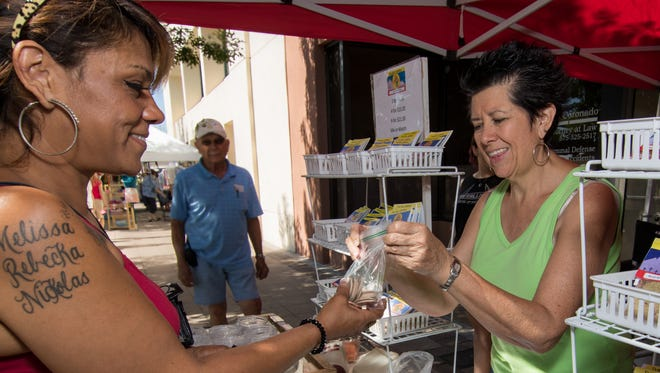 Karen Acosta-Lombino, a participant in the Double Up Food Bucks program, receives her bag of tokens from Brenda Mosely at the Las Cruces Farmers & Crafts Market.