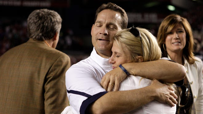 FILE - In this Oct. 1, 2011, file photo, Auburn coach Gene Chizik embraces his wife, Jonna, after his team's 16-13 victory over South Carolina in an NCAA college football game, in Columbia, S.C. After two years of living and working in Chapel Hill, N.C., while his wife and three children were in Auburn, Ala., Chizik has quit his job and returned home to be a full-time dad and husband. The lengthy long-distance relationship he had with his family is not uncommon among college football coaches as they job hop through a career with little security. (AP Photo/Brett Flashnick, File)