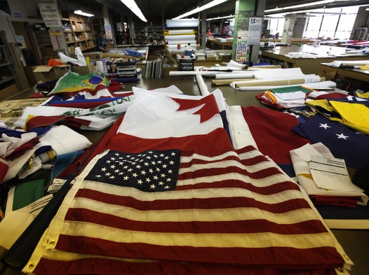An American flag banner sits among a few others waiting to be shipped from The National Flag Company, based in Cincinnati. The company began under a different name in 1869, initially specializing in printing. By 1894 flags became their primary product and on May 1, 1894, they changed the name of their business to The National Flag Company.