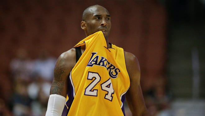 Los Angeles Lakers guard Kobe Bryant bites his jersey Oct. 21, 2014, in Anaheim, Calif.