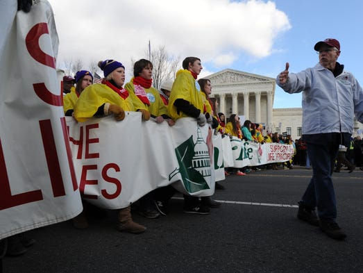Anti-abortion protesters pass the Supreme Court during